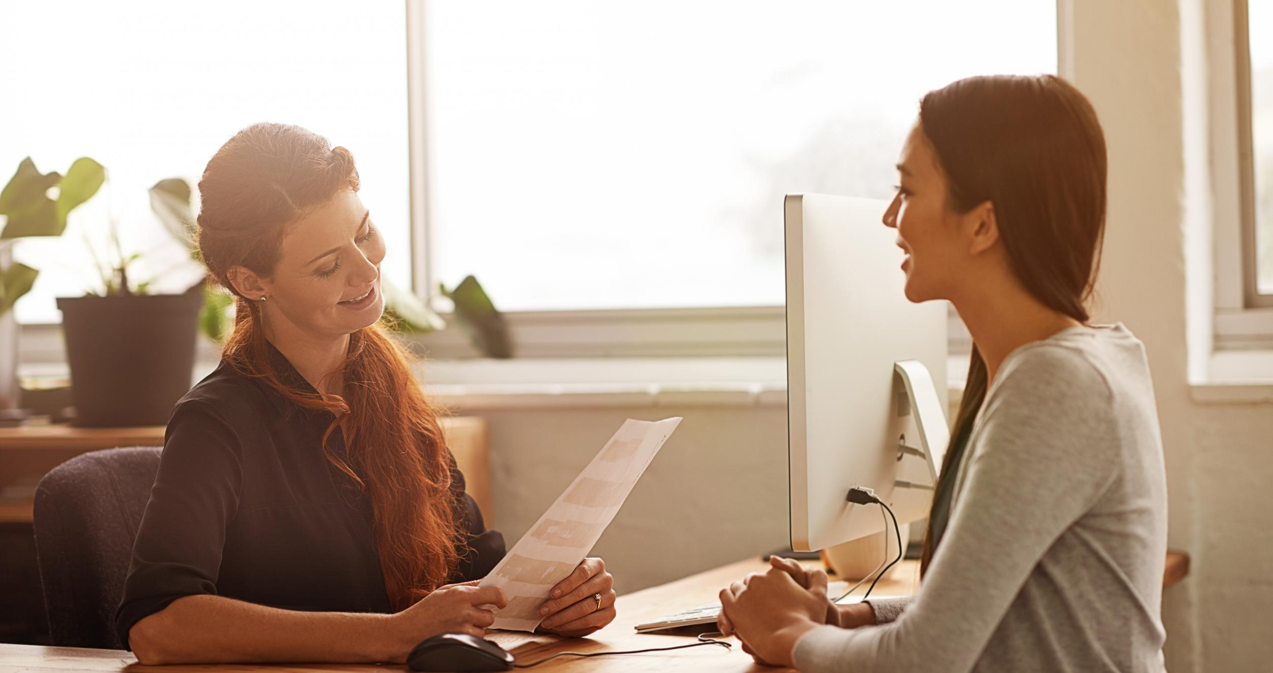 A woman conducts an interview for a female candidate