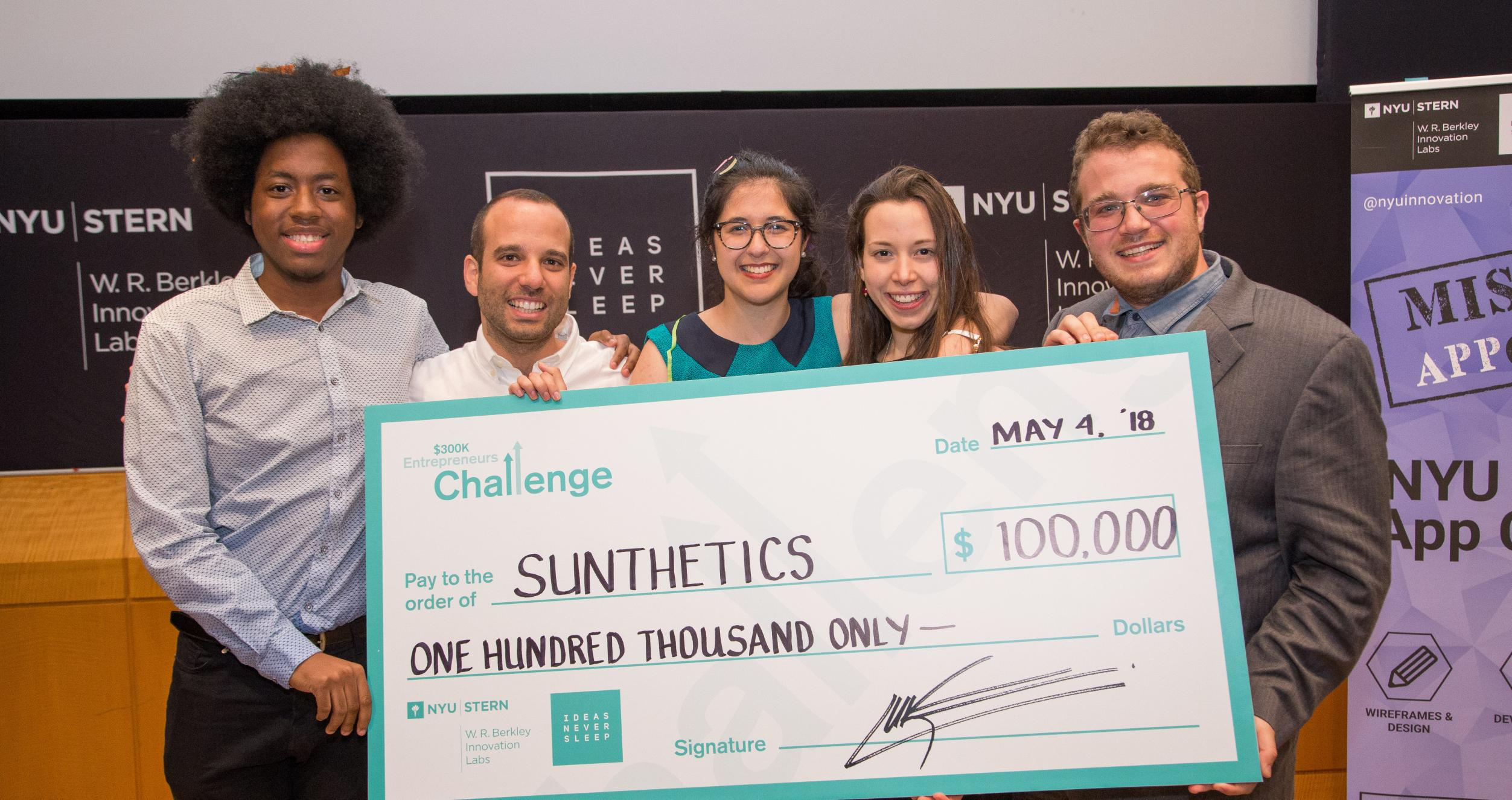 A team of five students holding a large check for $100,000 after winning a grand prize at the $300K Entrepreneurs Challenge