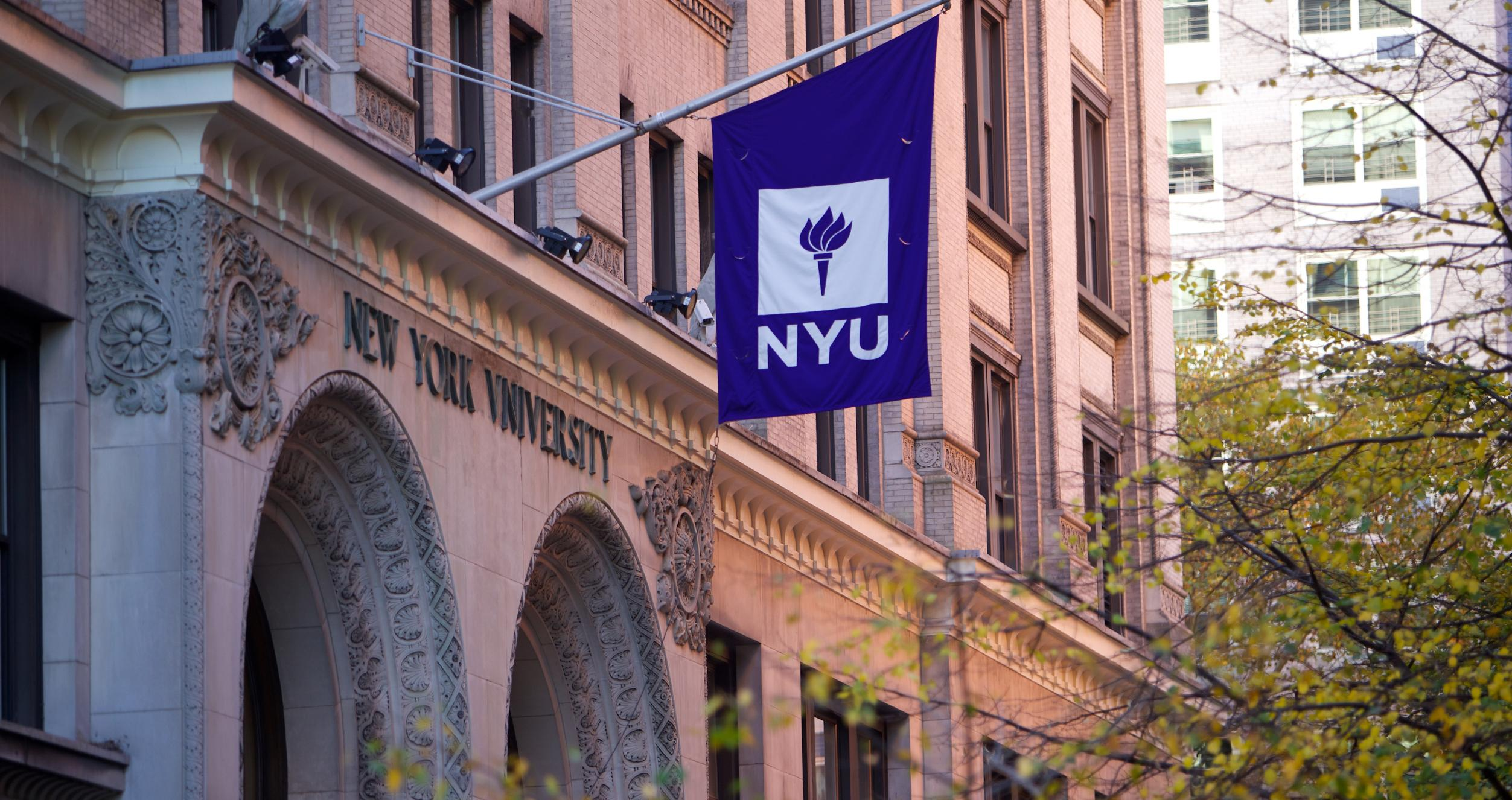 Entrance to Shimkin Hall with NYU flag above and trees on the right