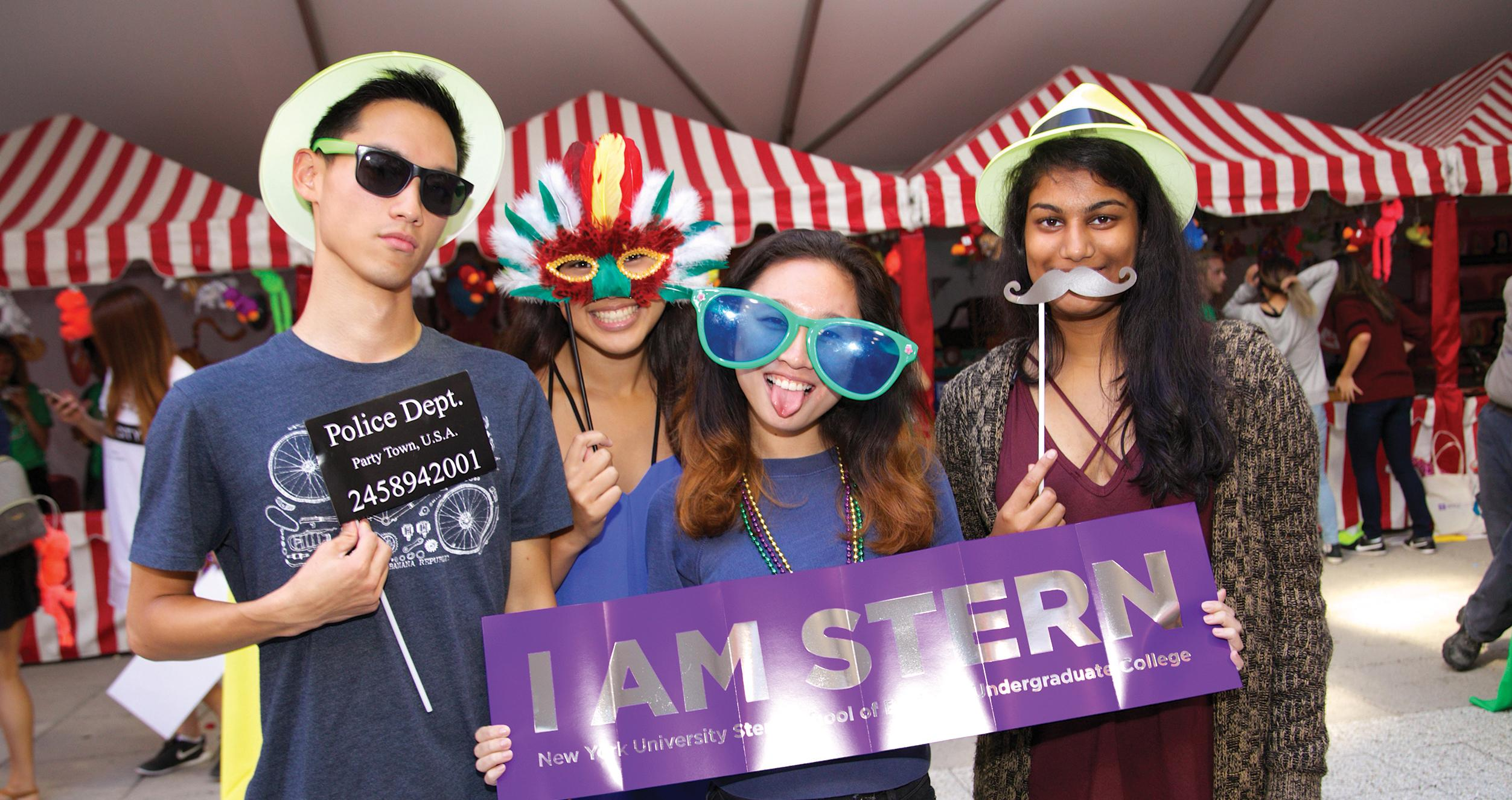 Students posing with props at Stern Block Party