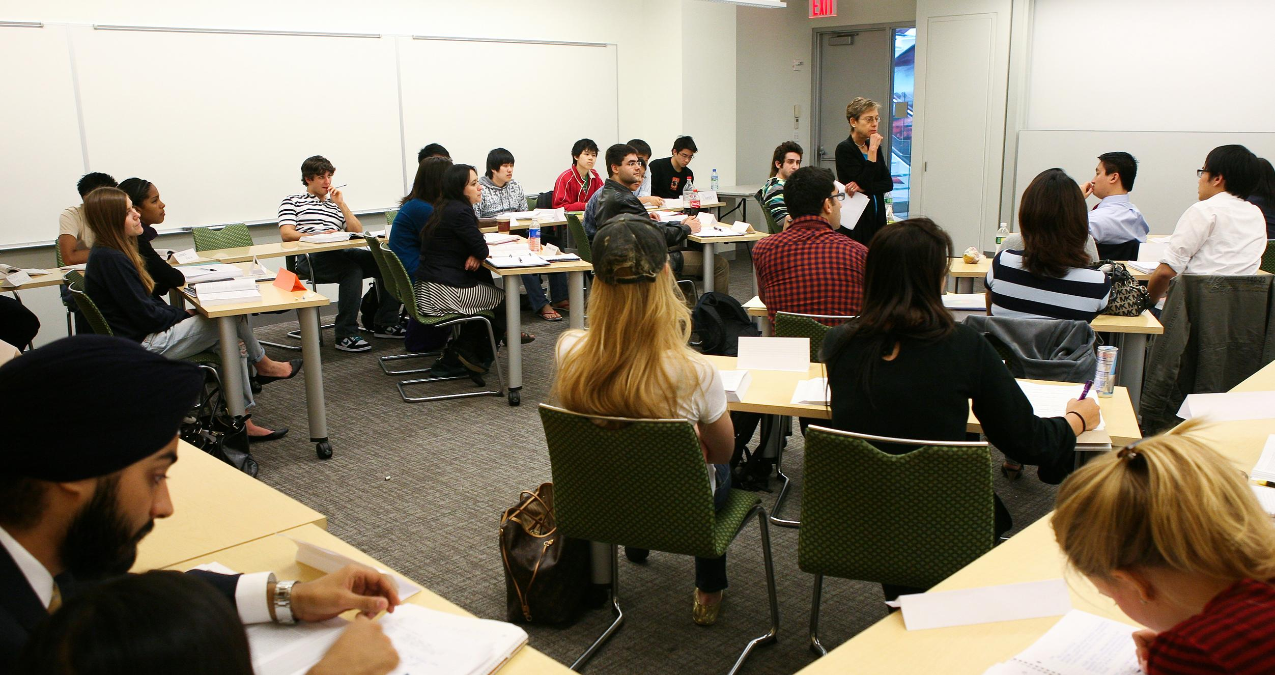 An NYU Stern professor teaches a small classroom of business students