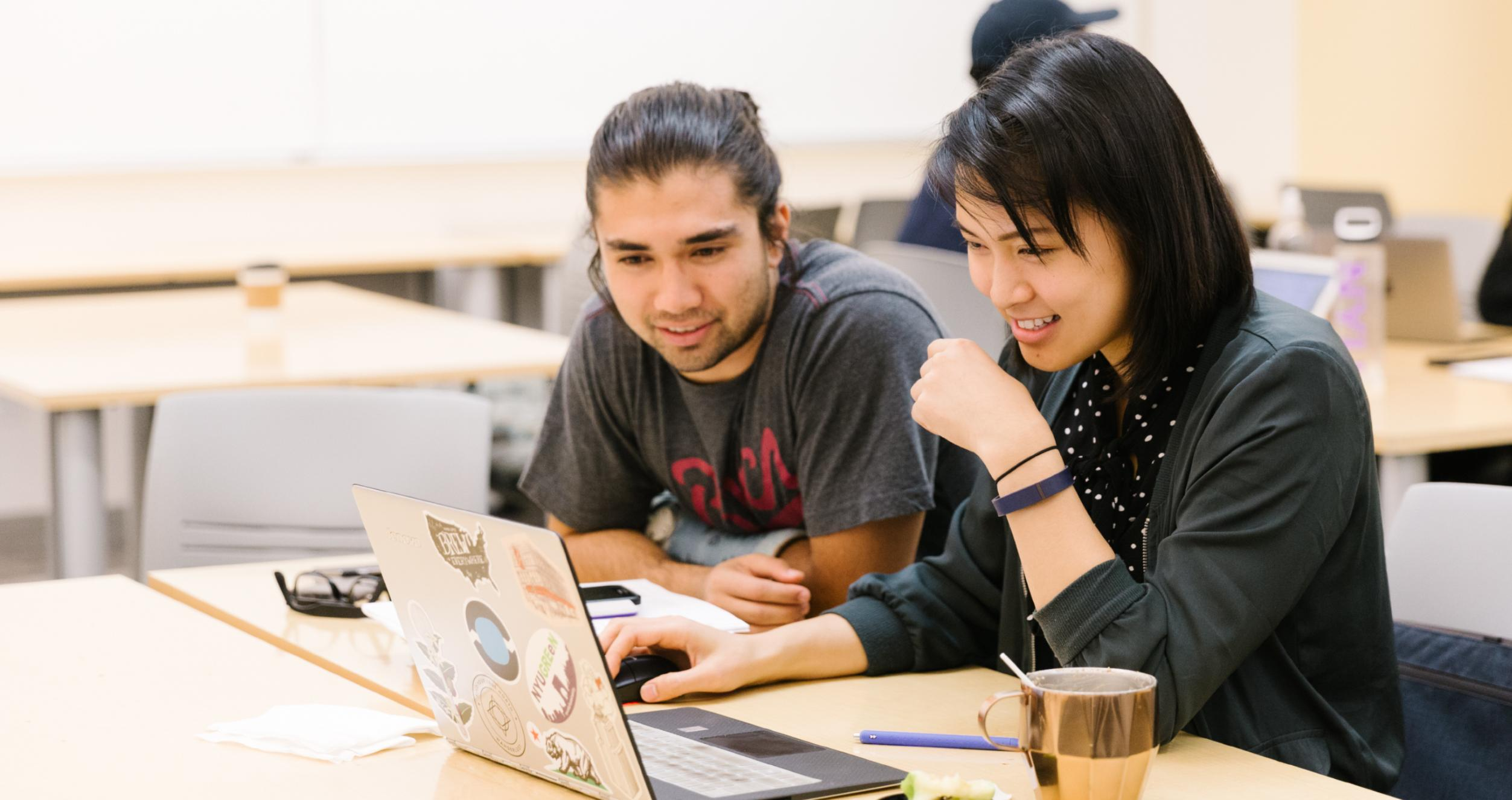 Two NYU Stern students are looking at a computer together in class