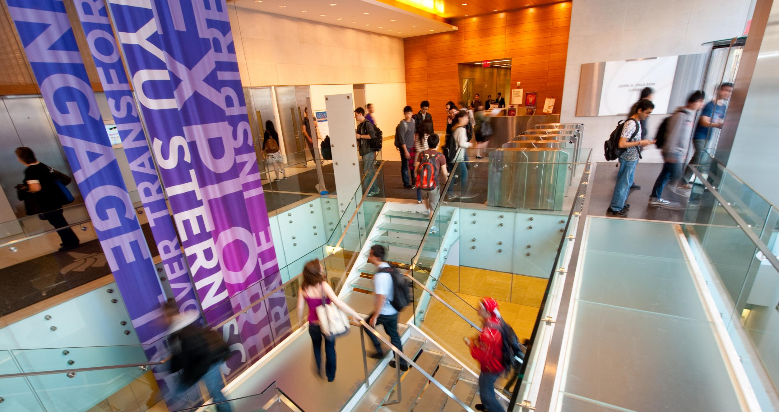 Students walking up the stairs in NYU Stern's Tisch Lobby
