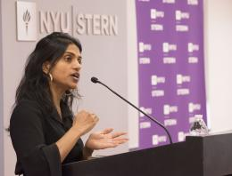 A woman speaking passionately at a podium in front of NYU Stern logo