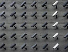 A brick wall filled with security cameras