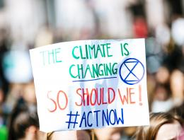 Person holding climate is changing poster