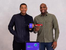 Two male founders holding a fake car and an app.
