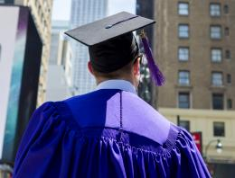 Graduate in cap and gown looking at Empire State Building