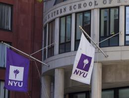 Two NYU flags hanging at NYU Stern's Gould Plaza