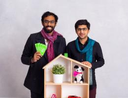 Two male founders in front of a play house.