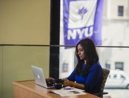 Woman sitting in front of laptop at desk with NYU flag outside in the background