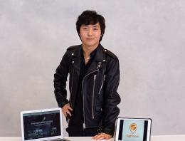 A photo of a male founder smiling in a leather jacket by both a laptop and an iPad.