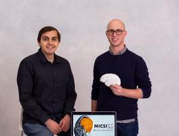 This is an image of two founders posing for a photo and holding a fake brain.