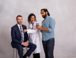This is a photo of three founders: one is in a suit sitting on a chair, one is a doctor and one is looking at a cell phone.