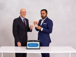 This is a photo of two male founders, one holding a tooth brush, one holding fake teeth.