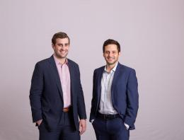 This is a photo of two male founders standing for a professional photo.