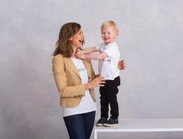 This is a photo of an adult female playing with a male toddler on top of a white table.