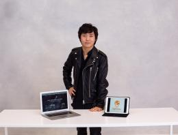 This is an image of a male founder at a white table with both a laptop and tablet open.
