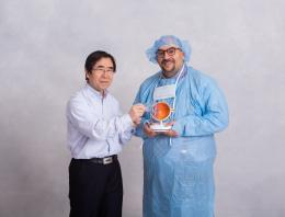 This is a photo of two founders, one of which is in hospital scrubs holding a model human eye.