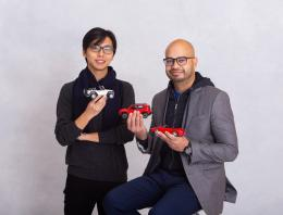 This is a photo of two male founders holding toy cars.