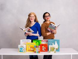 This is a photo of two female founders with a collection of books at a table.