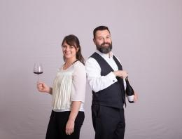 A photo of two founders holding a glass and a bottle of wine.