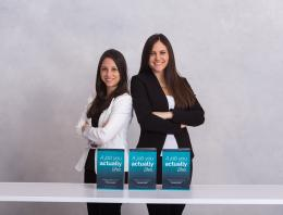 Two female founders are standing by a table.