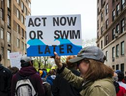 woman holding act now or swim later poster at NYC march for science