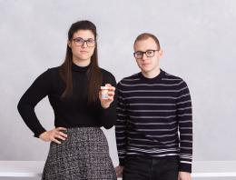Two founders (a male and a female) holding a pill bottle.