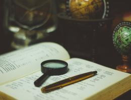 Book with magnifying glass and pen