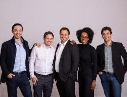 This is an image of 5 individuals on the dotted square team standing in front of a backdrop posing for a team photo.