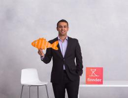 A founder stands with a fish cut out next to a table.