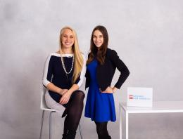 Two female founders are seated at a table.