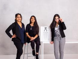 A team of three female founders sitting with an exam utilized by optometrists.
