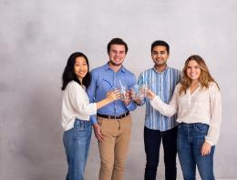 This is photo of four undergraduate founders holding cups and sustainable straws.