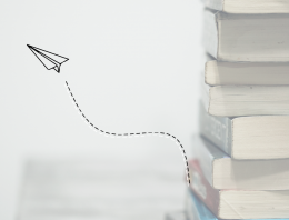 A pile of textbooks with an illustrated paper plane flying away