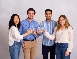 A photo of four founder holding mason jars.