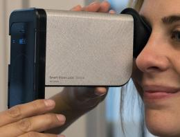Woman taking eye exam with hardware technology device on her right eye