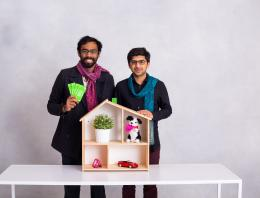This is an image of two male founders standing in front of a doll house.