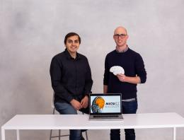 Team Micsi consists of two men standing at a white table holding a fake human brain.