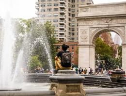 Student sitting near fountain in front of Washington Square Arch