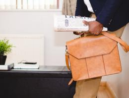 Person holding briefcase and newspaper