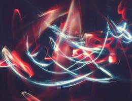 White and red light trails forming abstract patterns in a dark setting