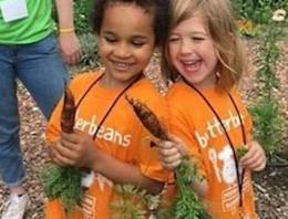 Two girls wearing orange shirts holding carrots