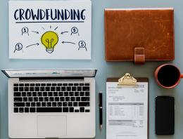 """MacBook Pro near neatly organized click pen, clipboard, coffee, phone, file holder, and doodle with the word """"crowdfunding"""""""