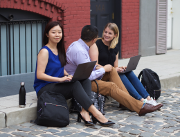 woman on curb with laptop