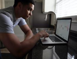 young man looking at graphs on computer screen