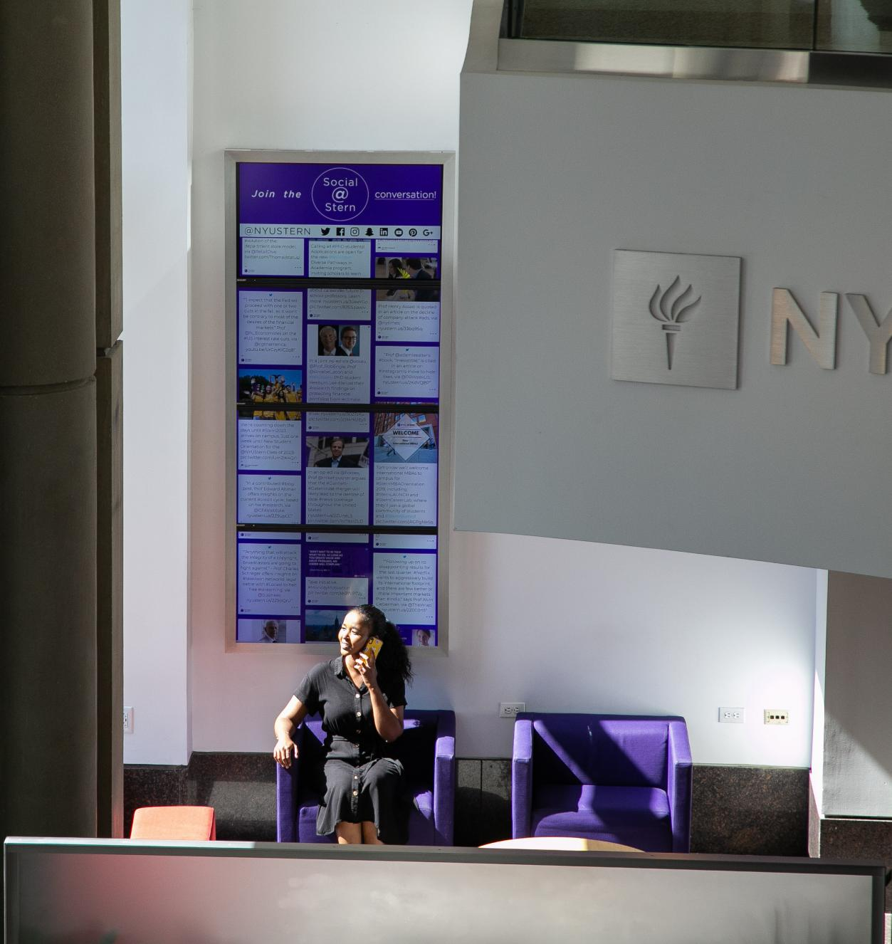 Woman on the phone sitting in a purple armchair in front of a screen displaying info cards with the NYU logo visible offside
