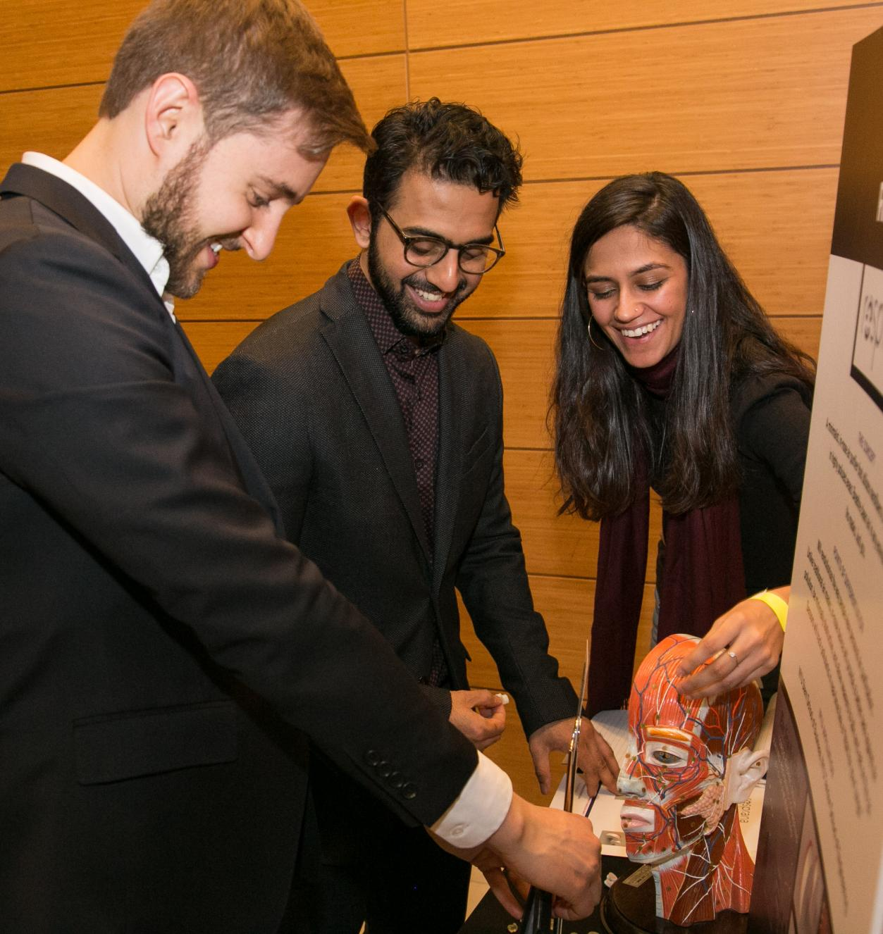 This is an image of three students at the Venture Showcase looking at a fake human skull.