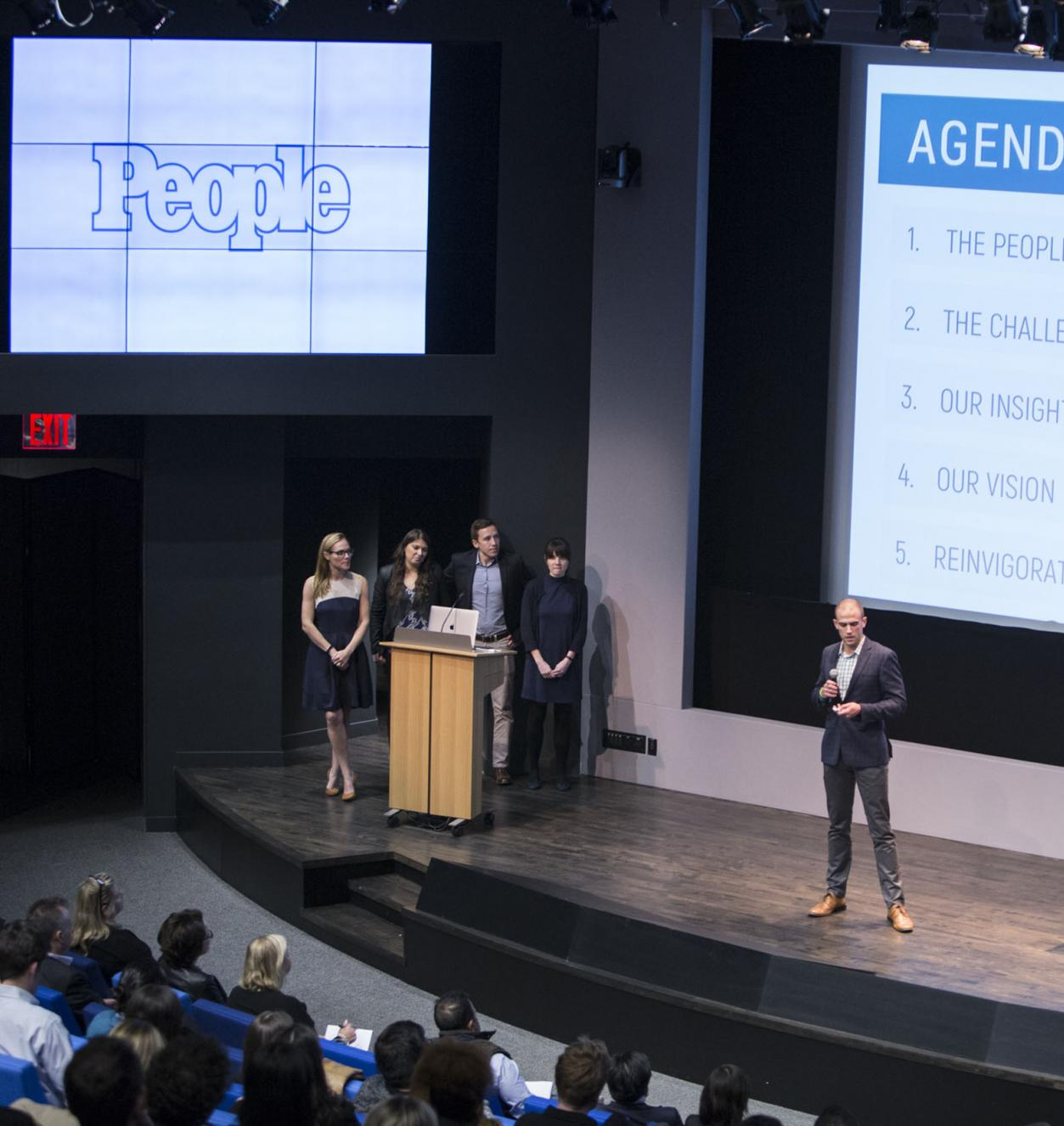 Four students presenting on a stage